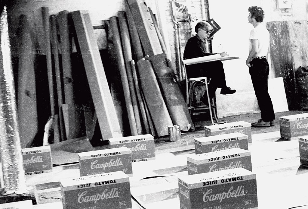 Andy Warhol and Gerard Malanga with Campbell's boxes at the Silver Factory, New York, 1964. Photograph by Billy Name
