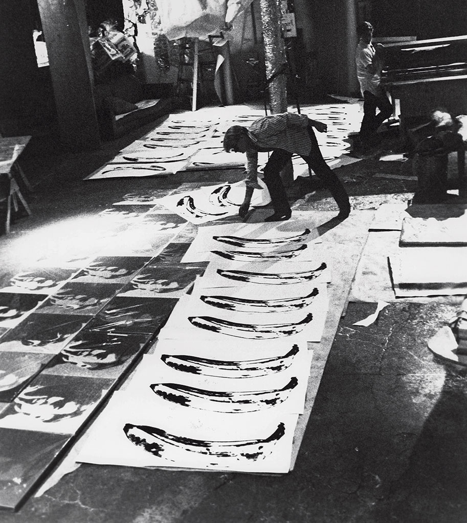 Andy Warhol handling banana prints and Gerard Malanga holding silk screen at the Silver Factory, New York, 1966. Photograph by Billy Name. Courtesy of 303 Gallery, New York.